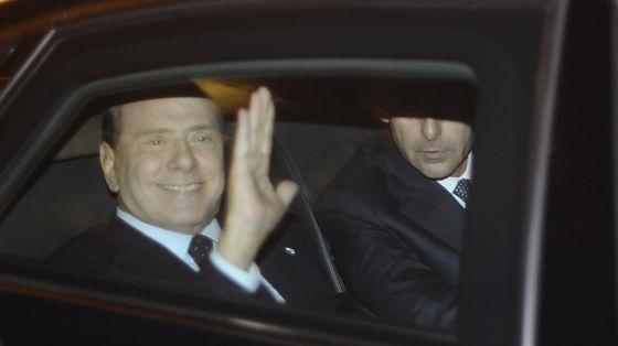 Silvio Berlusconi saluda a la salida de su residencia en Roma para dirigirse a presentar su dimisión al presidente Napolitano