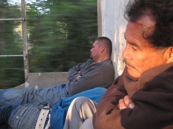 Amanece en La Bestia. Dos ilegales duermen en el vagón de carga mientras otro vigila que no se caigan.