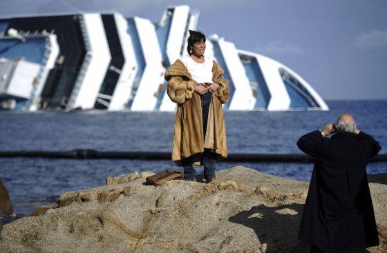 Una mujer posa frente al casco del 'Costa Concordia', que naufragó frente a la isla de Giglio el 13 de enero.