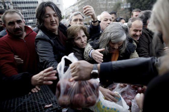 Campesinos griegos reparten fruta y verdura gratis en una plaza en Grecia.