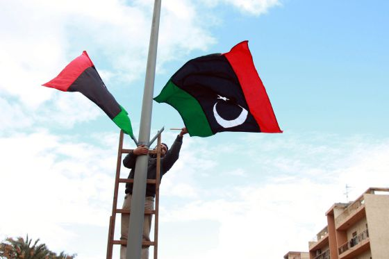 Un trabajador libio coloca banderas en Trípoli, en celebración para marcar el primer aniversario del inicio de la revuelta.