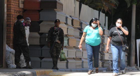 Dos mujeres pasan al lado de decenas de ataúdes apilados fuera del Instituto de Medicina forense de Comayagua (Honduras).