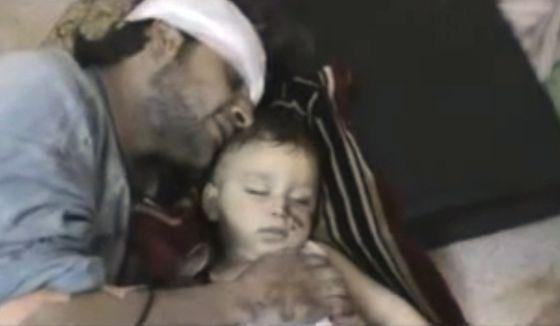 Un hombre herido llora sobre su hijo muerto en Homs.