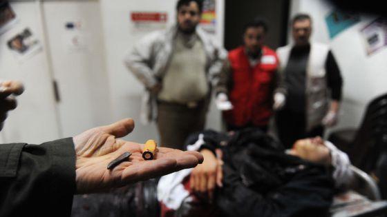 Un hombre muestra proyectiles ante un cadáver en la ciudad de Idlib.