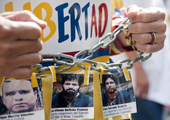 Un hombre muestra fotos de los policías secuestrados por las FARC en una multitudinaria protesta realizada contra esa guerrilla el pasado 6 de diciembre.