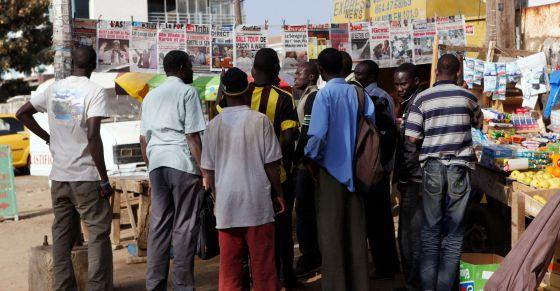 Ciudadanos senegaleses miran la prensa tras la publicación de los resultados de la primera vuelta de las elecciones presidenciales.