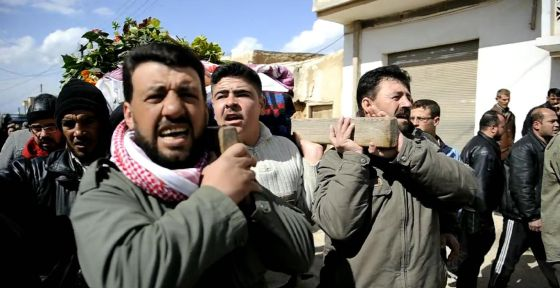 Varios hombres portan un cadáver en Qusayr, cerca de Homs.