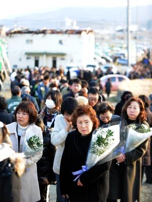Japoneses desfilan durante un acto de homenaje a las víctimas en la ciudad de Rikuzentakata, en la prefectura de Iwate.