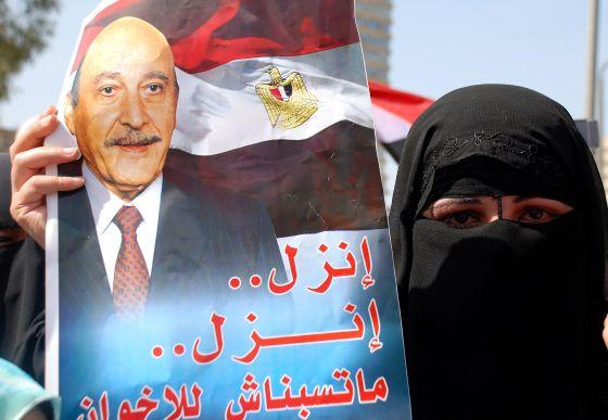 Una partidaria de Omar Suleiman sostiene un poster que lo llama a participar en las elecciones.