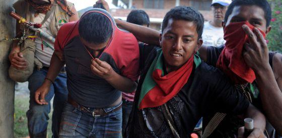 Un grupo de indígenas lleva detenido a un supuesto miembro de las FARC al que capturaron en Belén, en el Cauca, el miércoles.