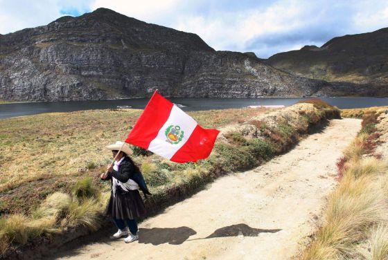 Una campesina ondea una bandera de Perú hoy, miércoles 18 de julio de 2012, en la laguna Namucocha, en Cajamarca (Peru).