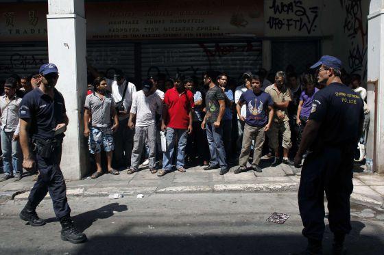 La policía detiene a un grupo de inmigrantes el domingo en el centro de Atenas.