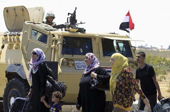 Varios palestinos de regreso Gaza pasan ante un tanque egipcio en el paso de Rafah el viernes.