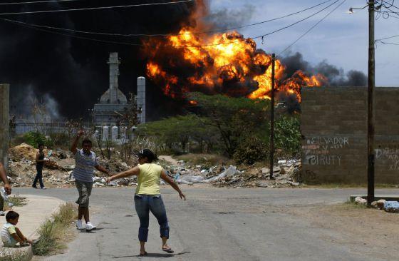 Vecinos de la barriada Alí Primera escapan de las llamas en la refinería de Amuay.