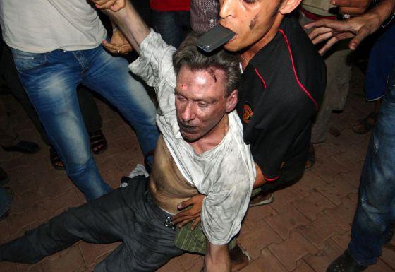 Un grupo de libios transportan a un hombre no identificado que se cree podría ser el embajador de EE UU en Libia.