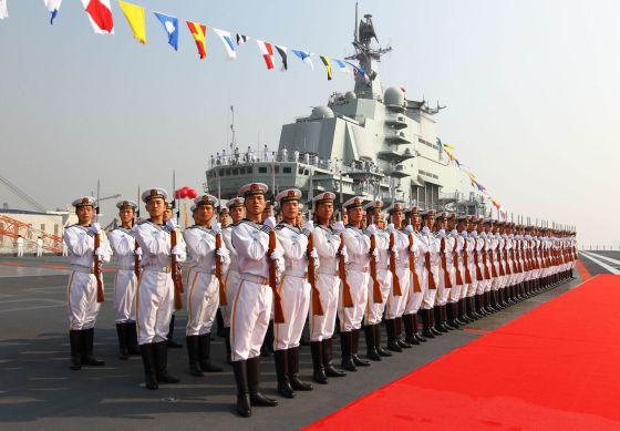 Soldados chinos junto al portaaviones Lianoning, en Dalian.