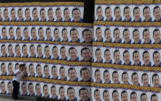 Un niño pasa junto a una pared llena de carteles electorales de Chávez.