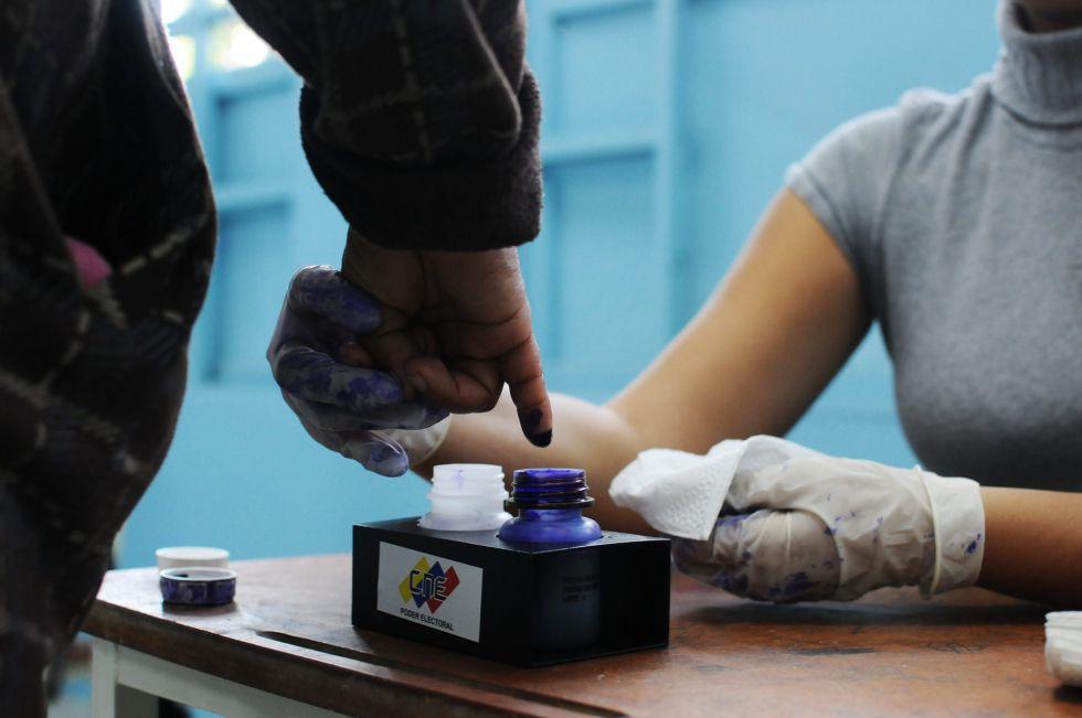 Una funcionaria marca con tinta el meñique a una electora que acaba de depositar su voto en la capital venezolana.