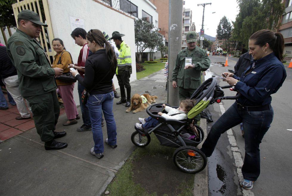 Venezolanos residentes en Colombia esperan para depositar su voto ante una oficina consular en Bogotá.