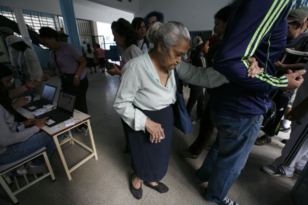 Una votante es ayudada a llegar hasta la urna en el barrio de Petare, en Caracas.