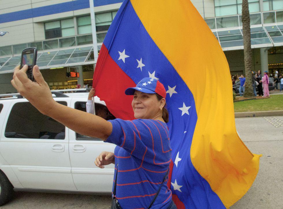 Cira Rodríguez, venezolana residente en Miami (Estados Unidos), se fotografía con la bandera de su país mientras espera para votar en Nueva Orleans, adonde han viajado cientos de compatriotas tras el cierre del consulado en la ciudad de Florida.