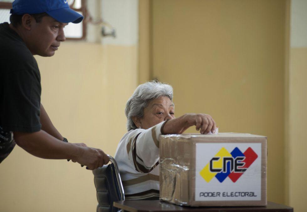 Una electora en silla de ruedas deposita su papeleta en el barrio caraqueño de 23 de enero.