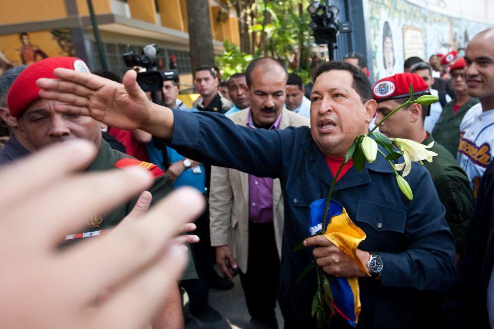 El presidente de Venezuela, Hugo Chávez, saluda a sus seguidores tras depositar su voto en un colegio de la zona popular del 23 de Enero.