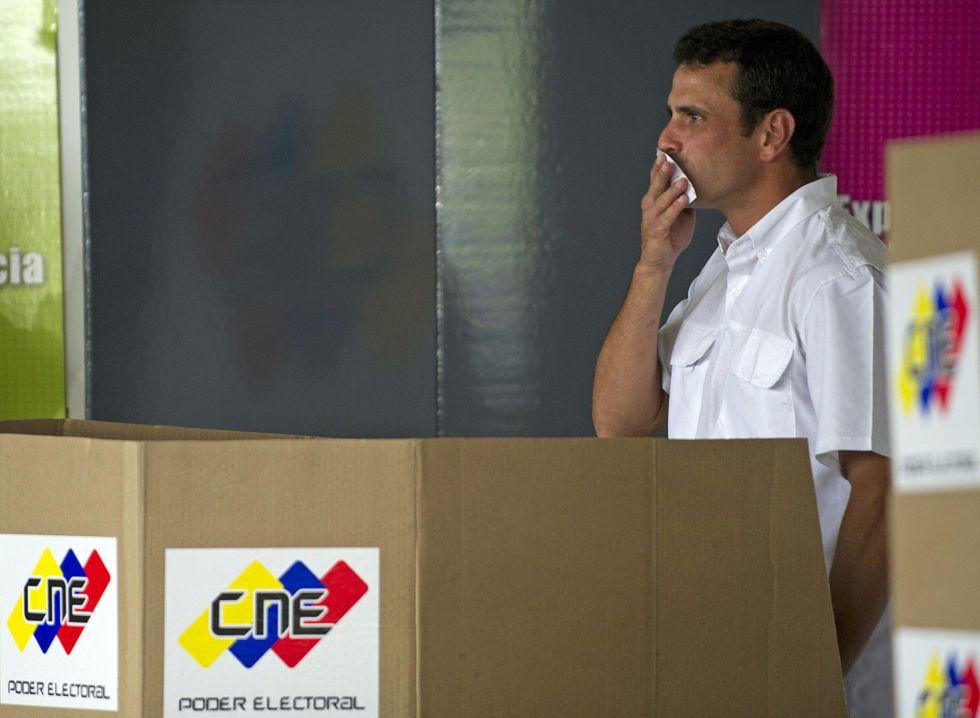 El candidato opositor Henrique Capriles besa su papeleta antes de votar este domingo en un colegio de Caracas.