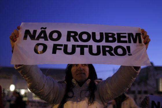 """Una manifestante con una pancarta donde se lee """"No robéis el futuro"""", en una protesta contra los recortes en Lisboa, en diciembre."""