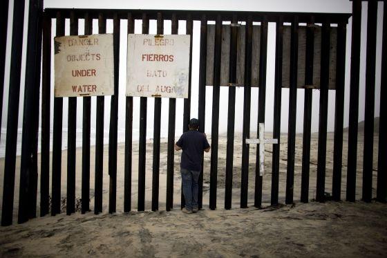 Un hombre mira a través del muro fronterizo entre México y Estados Unidos, en playas de Tijuana (México).