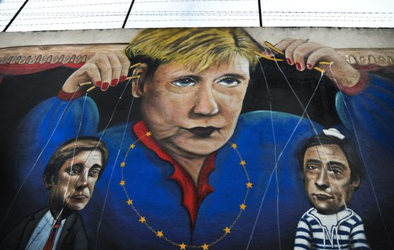 Un grafiti en una calle de Lisboa que muestra a la canciller alemana Angela Merkel controlando como títeres al primer ministro y ministro de exteriores de Portugal.