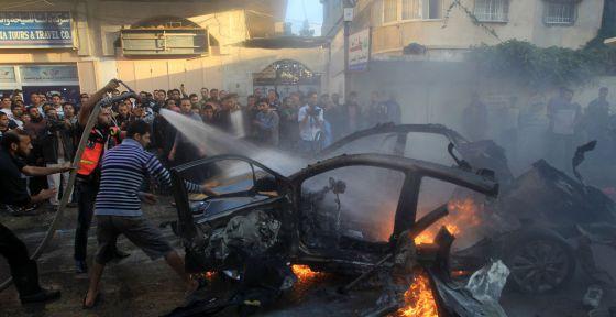 Varios hombres tratan de apagar el fuego del vehículo de Yabari.