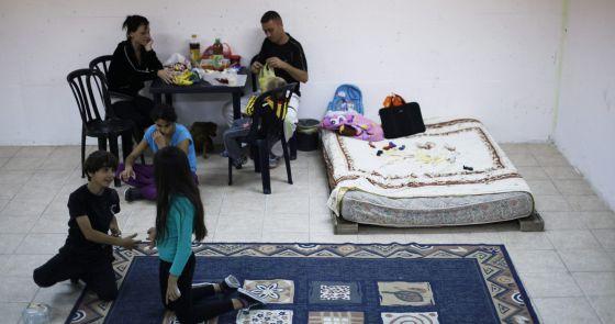 Una familia israelí, en el refugio aéreo de su casa de Ashkelón.