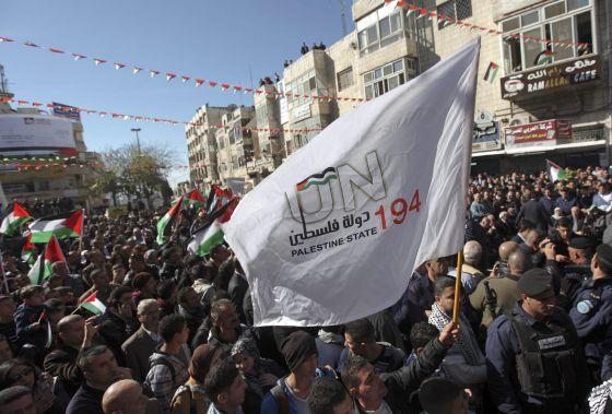Palestinos ondean una bandera durante una manifestación en Hebrón.