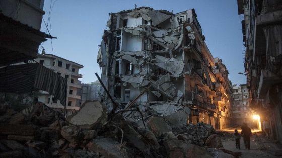 Un par de personas camina junto a un edificio bombardeado en Alepo.