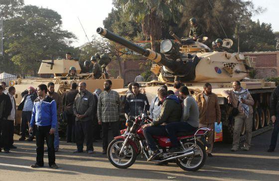 Un grupo de partidarios de los Hermanos Musulmanes, junto a los tanques que vigilan los muros del palacio presidencial de El Cairo.