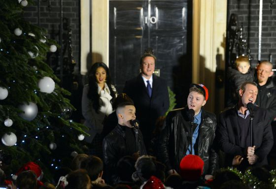 El primer ministro David Cameron (centro) minutos antes de encender el árbol de navidad frente a Downing Street 10, su residencia oficial.