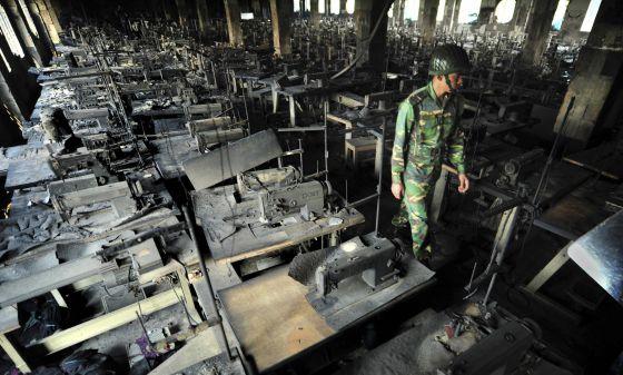 Un policía inspecciona unos talleres de confección de ropa tras incendiarse en Dacca (Bangladesh), el pasado noviembre.
