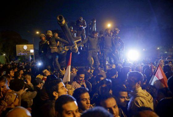 Soldados egipcios subidos a un tanque ante el palacio presidencial egipcio entre una multitud contraria a Morsi.