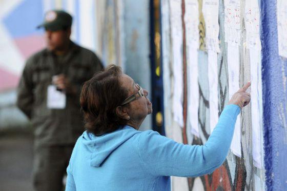 Una mujer busca su mesa de votación para participar en las elecciones.