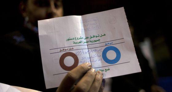 Un interventor de Giza muestra un voto nulo en la consulta constitucional.