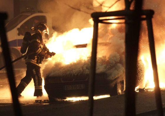 Un bombero intenta apagar el incendio en un coche en Nochevieja en Estrasburgo.