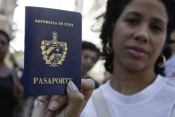 Una mujer muestra su pasaporte en una cola frente a una oficina en La Habana, el viernes.