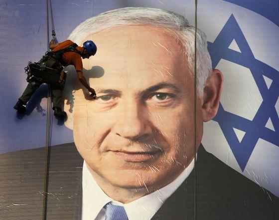 Un trabajador coloca en Tel Aviv un cartel de la campaña electoral de Netanyahu.