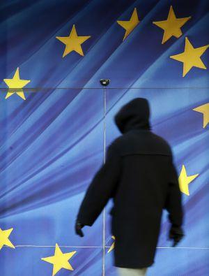 Un ciudadano pasea junto a la bandera de la UE de la fachada de la Comisión Europea, en Bruselas.