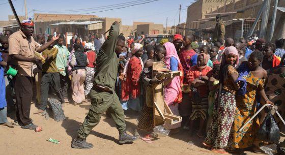 Un soldado maliense intenta dispersar una multitud que asalta una tienda perteneciente a un vecino árabe, en Tombuctú.rn
