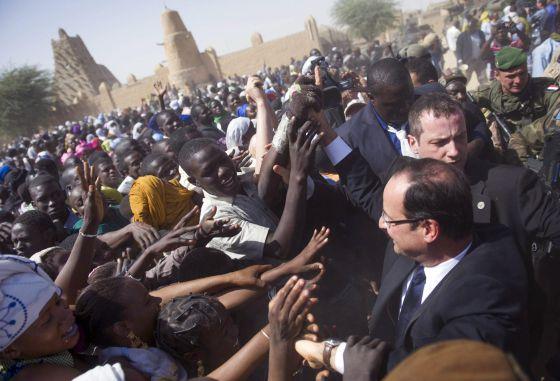 Un grupo de malienses reciben al presidente François Hollande en Tombuctú.