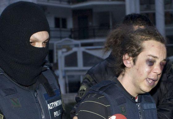 Un policía escolta a uno de los detenidos, el viernes en Kozani.