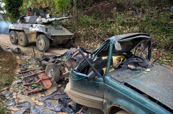 Una tanqueta pasa junto a un coche bomba en Cauca el martes.