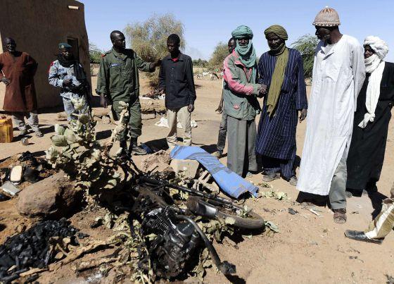 Un grupo de hombres contempla los restos de la moto utilizada por el suicida.